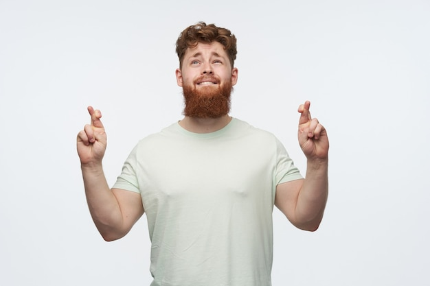 赤毛のひげを生やした男の肖像画、空白のtシャツを着て、彼の指を交差させ、白で良い結果を祈る