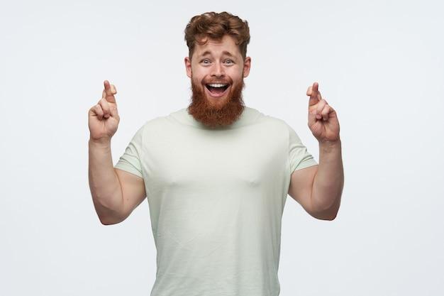 赤毛のひげを生やした男の肖像画、空白のtシャツを着て、彼の指を交差させ、良い結果を祈る
