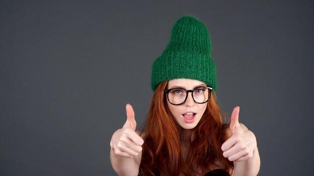 Портрет рыжая студентка с широкой улыбкой, глядя на камеру с счастливым выражением, показывая пальцы вверх обеими руками