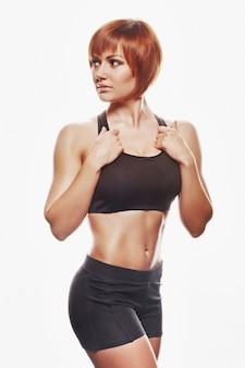 스포츠에서 빨간 머리 여자의 초상화입니다. 스튜디오 촬영, 절연, 흰색 배경