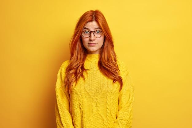 빨간 머리 젊은 유럽 여자의 초상화는 놀라움에서 눈을 뜨고 광학 안경과 캐주얼 점퍼를 착용하는 경이로 보입니다.