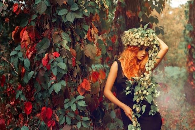 森の中で屋外の頭にホップの花輪を持つ赤毛の少女の肖像画