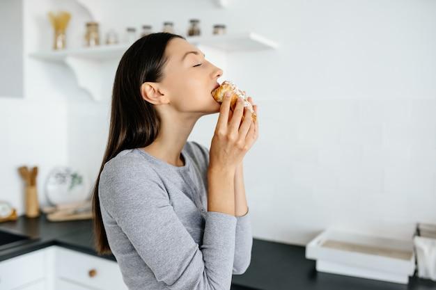 喜んでいる女性の肖像画は、家でおいしいクロワッサンを食べます。不健康な食品の概念。