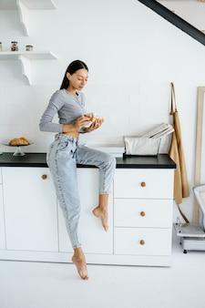 喜んでいる女性の肖像画は、家でおいしいクロワッサンを食べます。