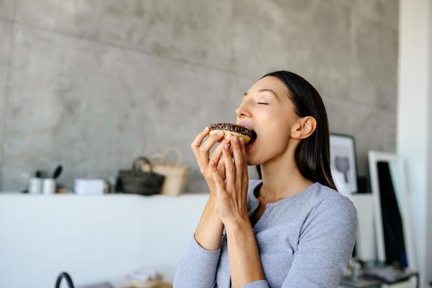 喜んでいる女性の肖像画は、家でおいしいドーナツを食べます。不健康な食品の概念。