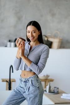 家でおいしいドーナツを保持している喜びの女性の肖像画。不健康な食品の概念。