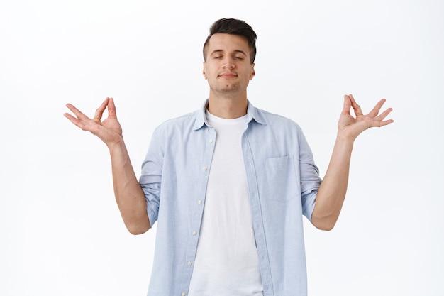 瞑想しているリラックスした平和な笑顔のハンサムな男の肖像画、深くてのんきな呼吸を閉じて、禅蓮のポーズで横に手を広げ、涅槃の練習ヨガ、白い壁に到達します