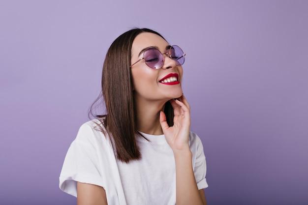 目を閉じて笑っている明るいメイクでリラックスしたヨーロッパの女性の肖像画。孤立したサングラスで快適な白人女性の屋内写真。