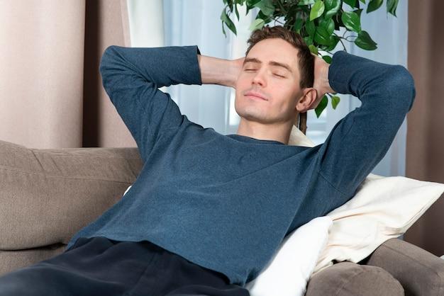 リラックスした幸せな男の肖像画で昼寝をしている休憩男を楽しんで眠っている若いハンサム