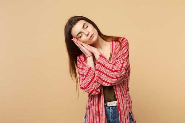 スタジオでパステルベージュの壁の背景に分離された顔の近くで手で寝ているカジュアルな服を着てリラックスした若い女性の肖像画。人々の誠実な感情、ライフスタイルのコンセプト。コピースペースをモックアップします。