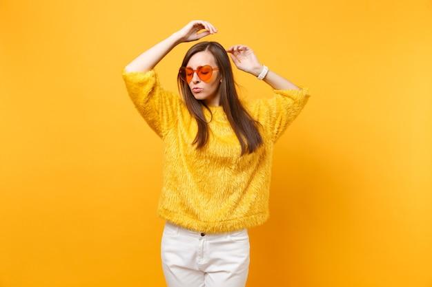 모피 스웨터, 흰색 바지, 하트 오렌지색 안경을 쓴 편안한 젊은 여성의 초상화는 밝은 노란색 배경에 고립되어 있습니다. 사람들은 진심 어린 감정, 라이프 스타일 개념입니다. 광고 영역입니다.