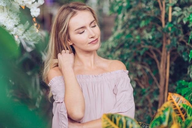 녹색 식물 가운데 서 편안한 젊은 여자의 초상화