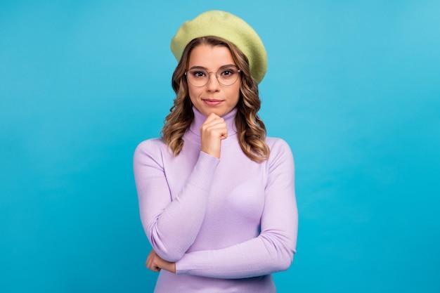 Портрет надежной девушки-работника босса трогает подбородок на синей стене