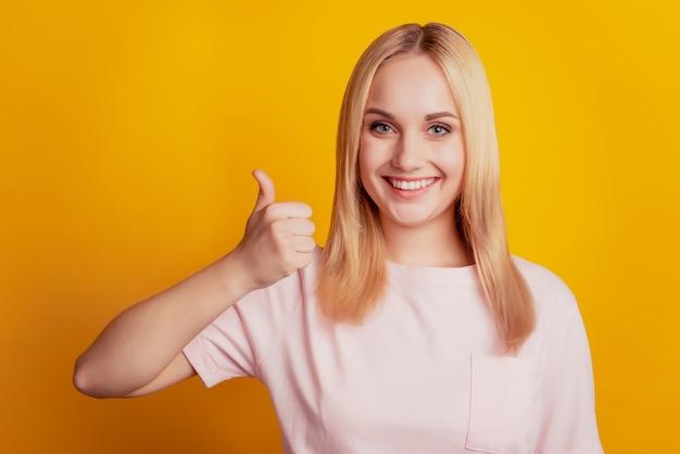 신뢰할 수 있는 발기인 여성 이빨 미소의 초상화는 노란색 배경에 엄지손가락을 들어 올립니다