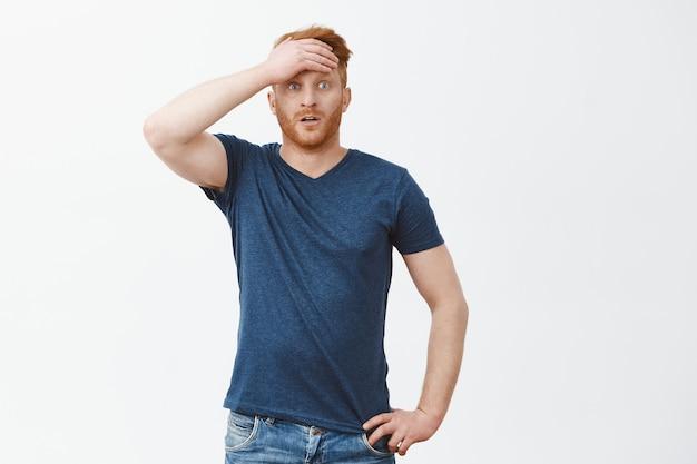 Портрет облегченного парня, приходящего в себя после шока и нервных переживаний, вытирающего пот со лба, смотрящего вытаращенными глазами, держащего руку на талии над серой стеной
