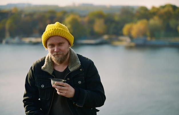 Портрет отдыхающего авантюриста с термосом металла горячего напитка на озере.