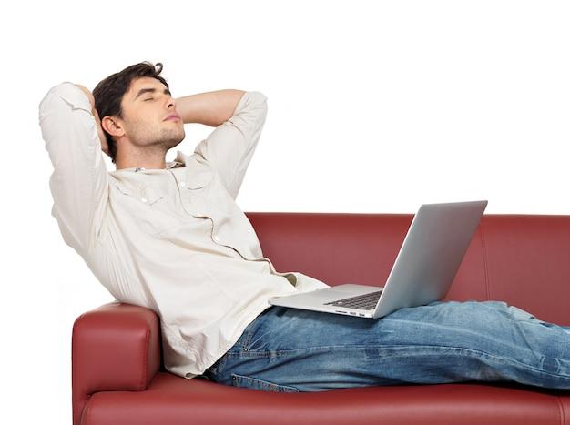 ノートパソコンを持って休んでいる男の肖像画は、白で隔離されたソファに座っています。