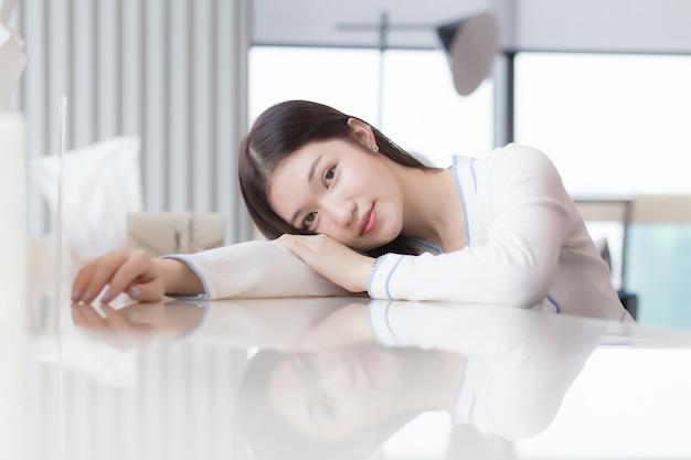 落ち着きのない美しい若い女性の肖像画は疲れを感じて机の上に横たわっています