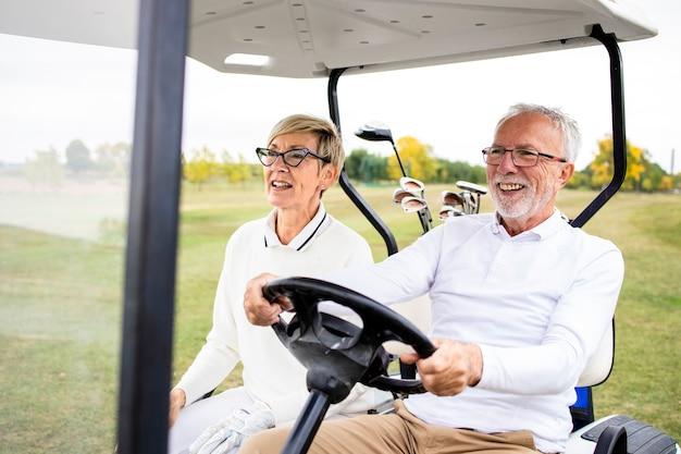 Портрет пожилой пары на пенсии, ведущей машину для гольфа в зеленую зону и наслаждающейся свободным временем на открытом воздухе