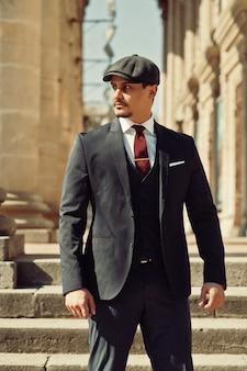 Портрет английского арабского бизнесмена в стиле ретро 1920-х годов в темном костюме, галстуке и плоской кепке возле старых колонн.