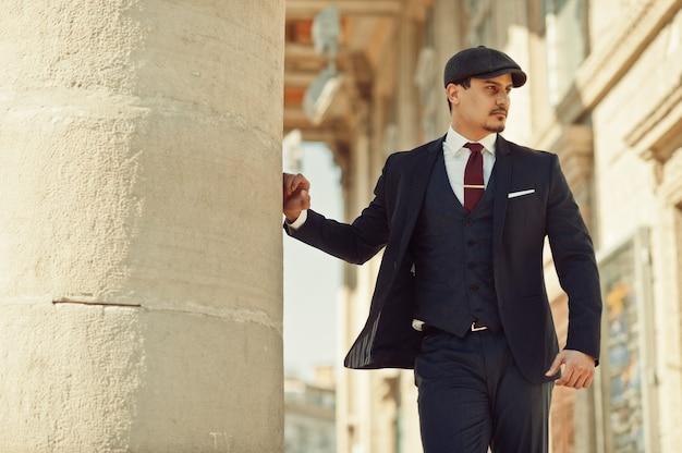古い柱の近くに暗いスーツ、ネクタイ、フラットキャップを身に着けているレトロな1920年代の英語のアラビアンビジネスの男の肖像画。