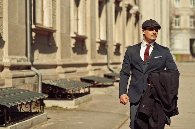 古い通りを歩いて暗いスーツ、ネクタイ、フラットキャップを身に着けているレトロな1920年代の英語のアラビアンビジネスの男の肖像画。