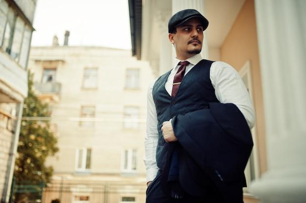 暗いスーツ、ネクタイ、フラットキャップを身に着けているレトロな1920年代の英語のアラビアンビジネスの男性の肖像画。 Premium写真