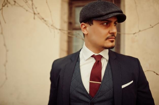 暗いスーツ、ネクタイ、フラットキャップを身に着けているレトロな1920年代の英語のアラビアンビジネスの男性の肖像画。