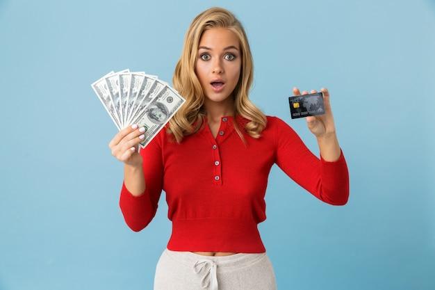 Портрет богатой девушки 20-х годов в красной рубашке с веером долларовых денег и кредитной карты, изолированной над синей стеной