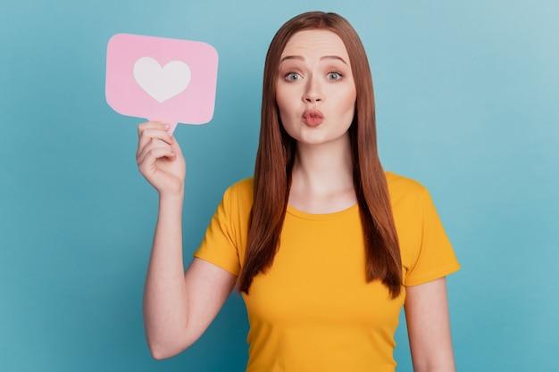 낭만적인 사랑스러운 여성의 초상화는 심장 아이콘 카드를 들고 파란색 배경에 공기 키스를 보냅니다.