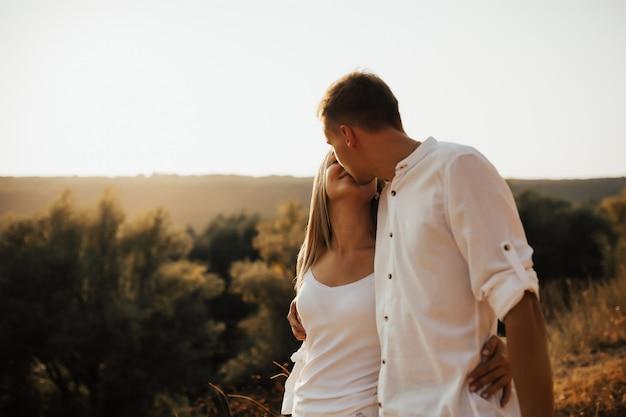 美しい風景の上でお互いを見て顔を抱いて白い服を着たロマンチックな魅力的なかわいいカップルの肖像画。