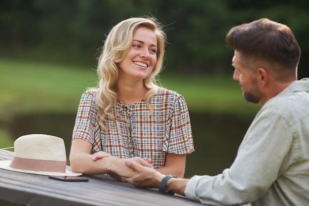 Портрет романтической пары, держащейся за руки и смотрящей друг на друга с любовью, сидя за столиком на берегу озера