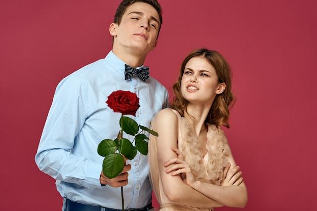 Портрет романтической пары в любви с красной розой на красном