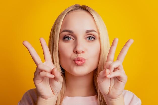 낭만적인 귀여운 소녀의 초상화는 노란색 배경에 공기 키스 손을 보여줍니다.