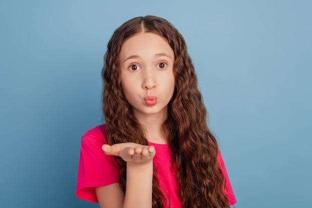 Портрет романтичной забавной милой маленькой девочки, держащей ладонь, посылает воздушный поцелуй на синем фоне
