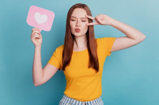 ロマンチックな女性の肖像画は、ボタンショーのようなハートカードを保持しますvサインカバー目を閉じて青い背景にエアキスを送信します