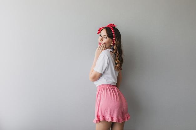 Портрет романтической дамы в пижаме, глядя через плечо. фотография в помещении со спины кудрявой девушки в розовых шортах.