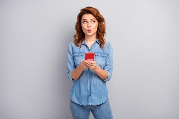 ロマンチックでポジティブな陽気なブロガーの女性の肖像画はスマートフォンを使用してコピースペースを使用します考えはテキストタイプのブログ投稿が欲しいと思いますデニムジーンズシャツ孤立した灰色の壁を着用してください