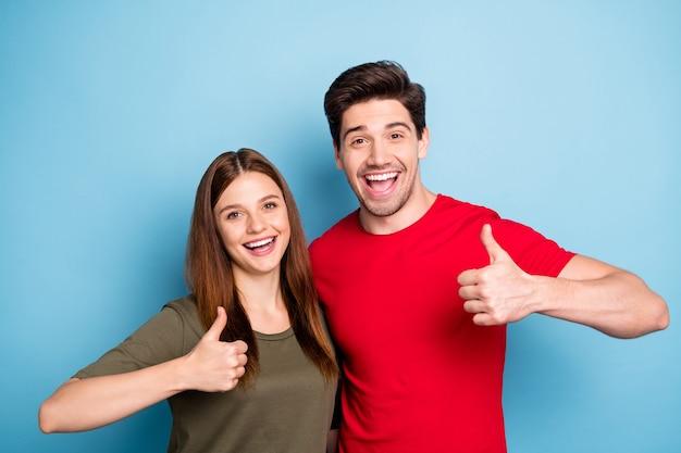 Портрет романтичных двух супругов, промоутеры показывают большой палец вверх знак решают, что реклама выбирает промо-совет, продажи носят зеленую красную футболку на синем фоне