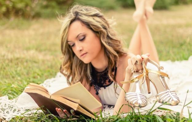 잔디 위에 누워 책을 읽고 손에 그녀의 신발과 함께 낭만적인 젊은 여자의 초상화. 신발에 선택적 초점입니다.