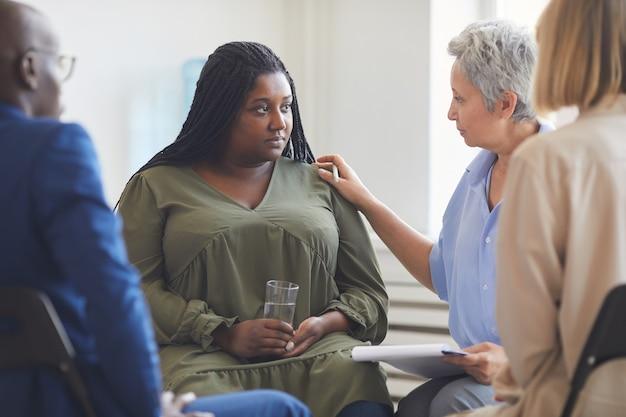サークルに座って彼女を慰める人々とのサポートグループミーティング中に心理学者に耳を傾ける悲しいアフリカ系アメリカ人女性の肖像画