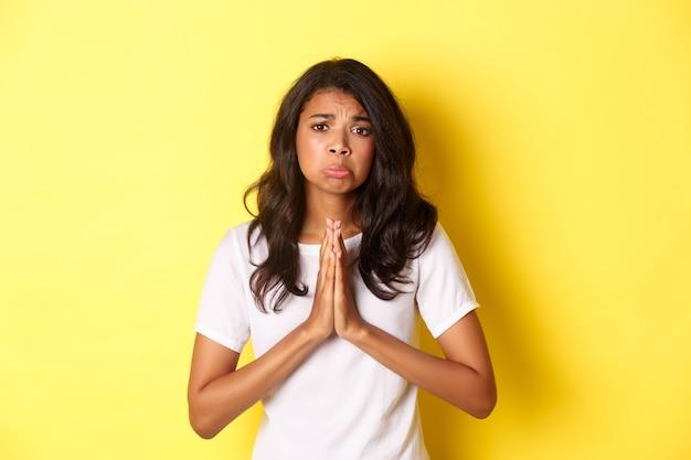 Портрет грустной афроамериканской девушки, умоляющей о помощи и надутой, стоящей над желтым ...