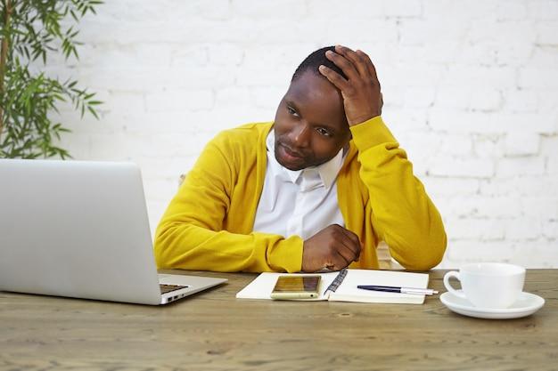 黄色のカーディガンを身に着けている悲しいアフロアメリカ人男性従業員の肖像画は、ラップトップ、コーヒー、日記を持って机に座って、仕事でストレスや失敗のために疲れて過労を感じて頭に触れています