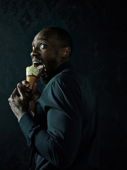 黒のスタジオの背景の上にアイスクリームを保持している悲しいアフロアメリカ人の肖像画
