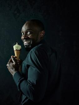 Портрет грустного афроамериканца, держащего мороженое над черной студией