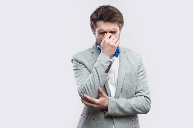 カジュアルな灰色のスーツと青い蝶ネクタイで立って、頭を下げて泣いている悲しい一人で落ち込んでいるハンサムなひげを生やした男の肖像画。明るい灰色の背景に分離された屋内スタジオショット。