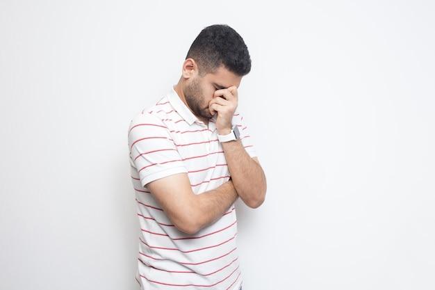 ストライプのtシャツを着て立って、頭を下げて泣いている悲しい一人のハンサムなひげを生やした若い男の肖像画。白い背景で隔離の屋内スタジオショット。