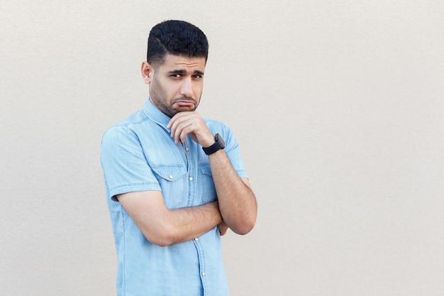 悲しみや心配そうな顔で立ってカメラを見ている青いシャツを着た悲しい一人でハンサムな若いひげを生やしたビジネスマンの肖像画。明るいベージュの壁の背景に分離された屋内スタジオショット。