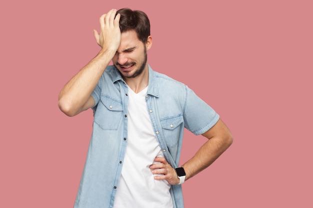 파란색 캐주얼 스타일 셔츠를 입은 슬픈 외로운 패자 수염이 난 청년의 초상화는 머리를 숙이고 무엇을 해야 할지 생각하고 있습니다. 실내 스튜디오 촬영, 분홍색 배경에 격리.