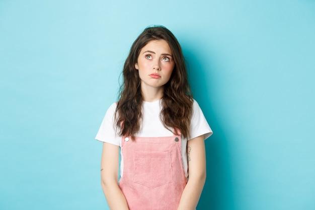 グラマーメイクで悲しくて暗い若いブルネットの少女の肖像画は、左上隅を動揺して思慮深く見て、不機嫌に感じ、青い背景に立っています。
